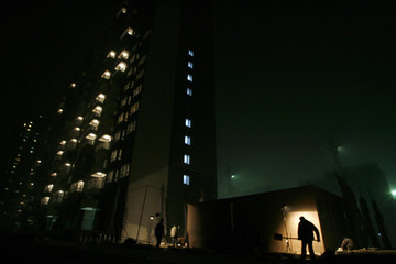 Men work at a residential construction site at night in Beijing
