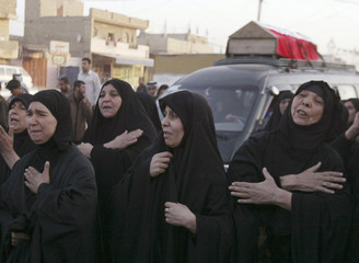 Women grieve during funeral for some of the pilgrims killed in Sunday's car bomb attack in Baghdad