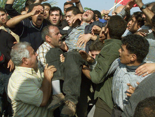 A RELATIVE IS CARRIED AWAY DURING A FUNERAL IN GAZA CITY.