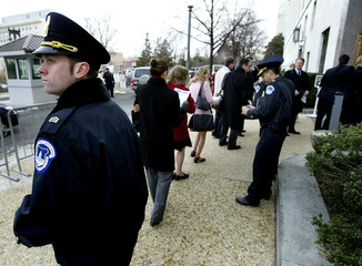 US CAPITOL POLICEMAN WATCHES WORKERS RETURN TO THE DIRKSEN SENATE BUILDING IN WASHINGTON.