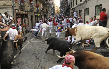 A runner is thrown by a Nunez de Cuvillo fighting bull at the Estafeta curve at the San Fermin festival in Pamplona