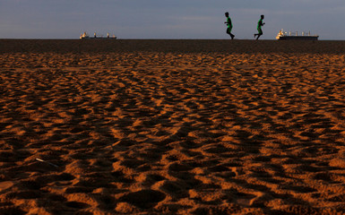 People jog at Iracema beach in Fortaleza, Brazil