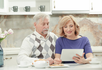 Cute elderly couple sitting in kitchen with tablet computer