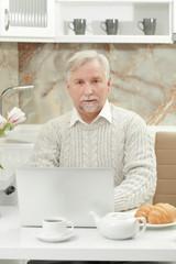 Elderly man sitting in kitchen with laptop