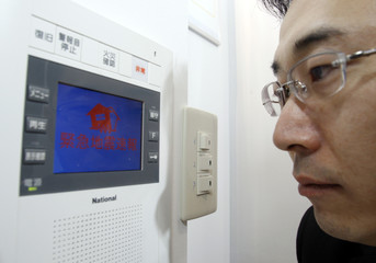 An employee of Tsunagu Network Communications looks at Scoop System, an earthquake alert system, during the Security and Safety Trade Expo in Tokyo