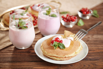 White plate with delicious pancakes, berries and glasses of yogurt on wooden table