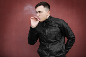 Handsome young man smoking weed outdoors on color background