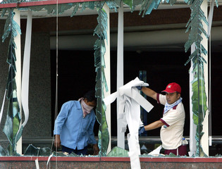 Indonesian workers clean up after bomb blast in Jakarta.
