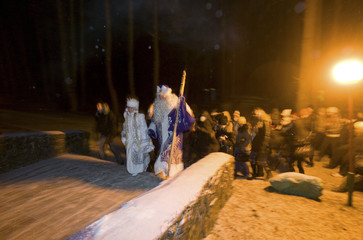 People dressed as Slavic mythical characters Father Frost and Snow Maiden walk during performance at children's hospital near village of Daubeni