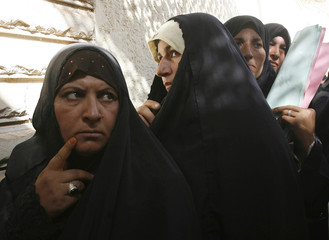 Residents wait at the entrance of a government office to ask for financial assistance in Samarr