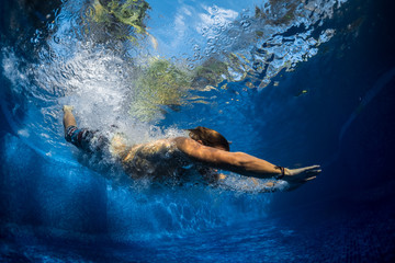 Underwater shot of the young man jumping in the pool