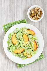 Fresh nectarine, cucumber and iceberg lettuce salad on plate with homemade croutons on the side, photographed overhead with natural light