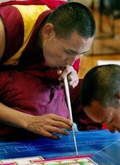 TIBETAN MONK GENTLY BLOWS SAND INTO PLACE WHILE CREATING A MANDALA.