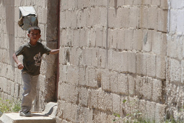 Palestinian child plays near his home at the Al-Baqaa Palestinian refugee camp, near Amman