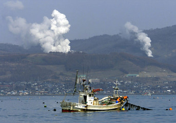 Fishermen on a fishing boat check scallop cultivation off Abuta at the foot of the smoking Mount Usu..