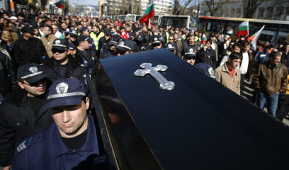 Bulgarian policemen carry a mock coffin during a rally in Sofia