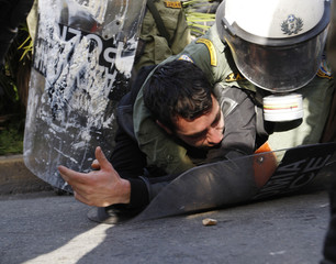Riot policemen arrest protester during clashes in front of police headquarters in Athens
