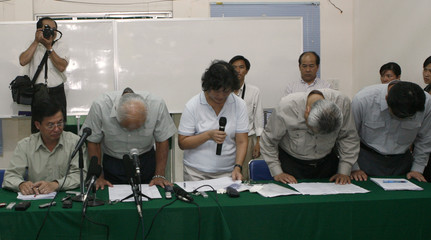 Japanese contractors bow while attending a news conference beside the scene of the bridge collapse in Mekong Delta's Vinh Long province