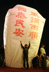 A man holds onto a 20-foot tall lantern during the traditional Chinese Lantern Festival in Taipei