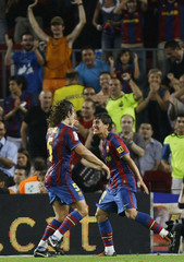 Barcelona's Bojan Krkic celebrates his goal with team mate Carles Puyol against Sporting Gijon during their Spanish first division soccer match at Nou Camp stadium in Barcelona