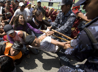 Riot police try to detain Tibetan activists during a protest outside the visa section of the Chinese embassy in Kathmandu