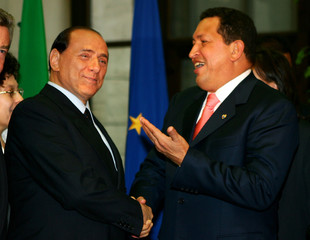Italian Prime Minister Silvio Berlusconi shakes hands with Venezuelan President Hugo Chavez in Milan