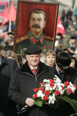 Communist Party leader Gennady Zyuganov walks with flowers as portrait of Stalin is seen in the background, at Red Square in Moscow