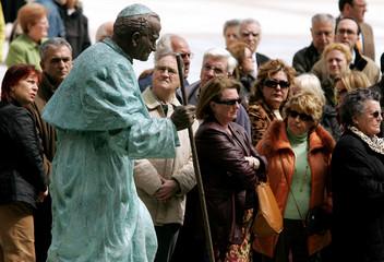 People gather around statue of Pope John Paul II in Oviedo
