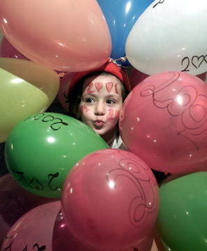 A YOUNG GIRL WEARS A 2001 LOGO ON HER FACE AS SHE PLAYS BETWEEN BALLOONS IN AMMAN.
