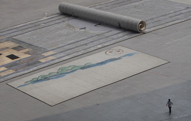Olympic volunteer walks past drawing on ground level of National Stadium at Olympic Green in Beijing