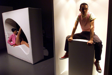 Two models sit in display boxes whilst wearing outfits designed by Australian Joe Saba during the Sa..