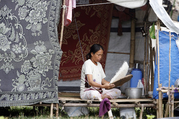 A woman winnows rice using a woven tray in a temporary shelter at an evacuation camp in Datu Piang