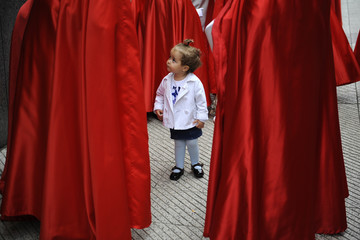 A child stands among the penitents of the 'Jesus Cautivo' brotherhood during a Holy Week procession in Oviedo