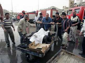 Residents carry the charred bodies of victims on a cart after a car bomb attack in Baghdad