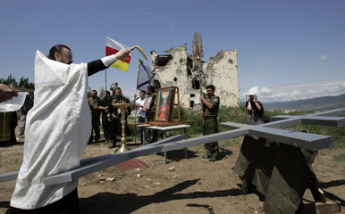A priest blesses a cross which will be installed in Tskhinvali
