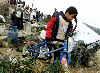 PALESTINIAN BOY CARRIES HIS BIKE THROUGH THE RUBBLE AND DEBRIS OF ISSASALEM DARABE'S HOUSE AFTER IT ...