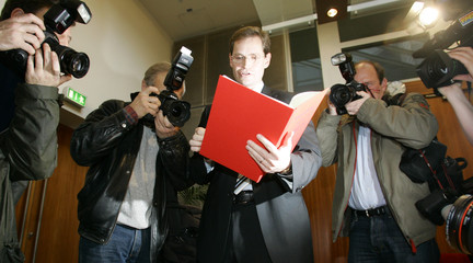 Chairman of Berlin's SPD Mueller is surrounded by photographers as he holds the coaltion agreement in Berlin
