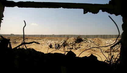 Palestinians boys play near the border (in background) between Egypt and the southern Gaza strip, in..