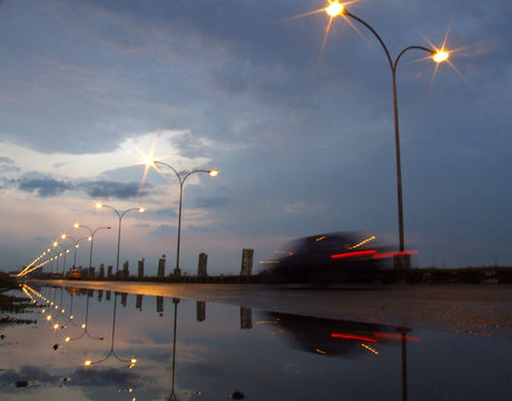 A car passes on a highway beneath pre-monsoon clouds in Kolkata