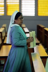 Indonesian nun brings candles back inside Santa Maria church in Nias.