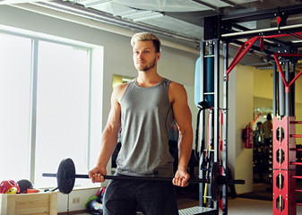 Sporty male in sportswear holds barbell over TRX stand background in a gym club.