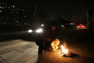 A man burns paper money in Beijing