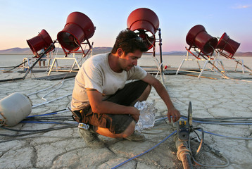 Organizer Camron Assadi inspects a fuel line as he prepares for a re-creation of the world's first n..
