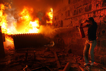 A Palestinian man tries to extinguish a fire during clashes with Israeli police in Jerusalem