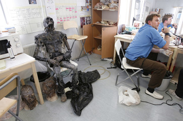 An actor prepares his makeup next to a skeleton prop in the makeup room on the set of the horror movie 'Dark Floors' in Oulu