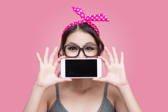 Beautiful young asian woman with pin-up make-up and hairstyle over pink background with mobile phone