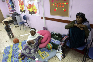 Residents sit in a bomb shelter during a rocket attack in Sderot