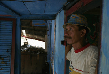 A villager stands inside his damaged house at Serangai village near the Indonesian city of Bengkulu