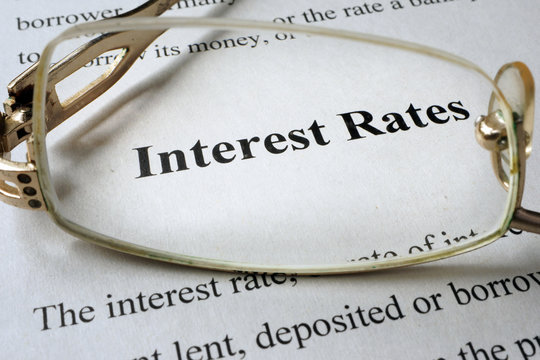 Page of paper with words interest rates and glasses.