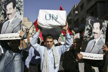 Jordanian protesters hold photographs of former Iraqi leader Saddam Hussein during a rally in Amman